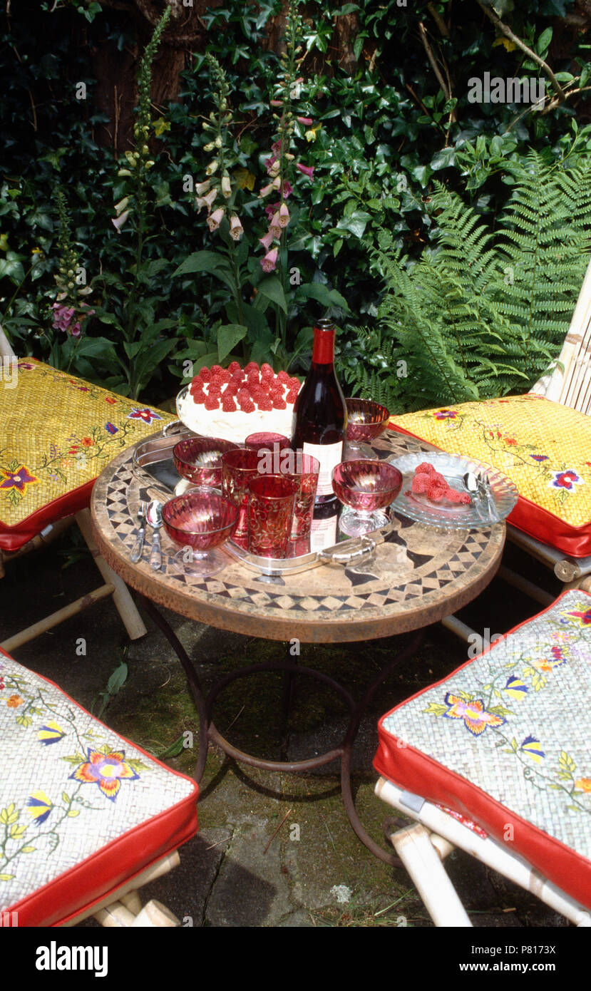 Raspberry Pavlova And Bottle Of Red Wine With Cranberry Glassware On Mosaic  Tiled Table On Patio