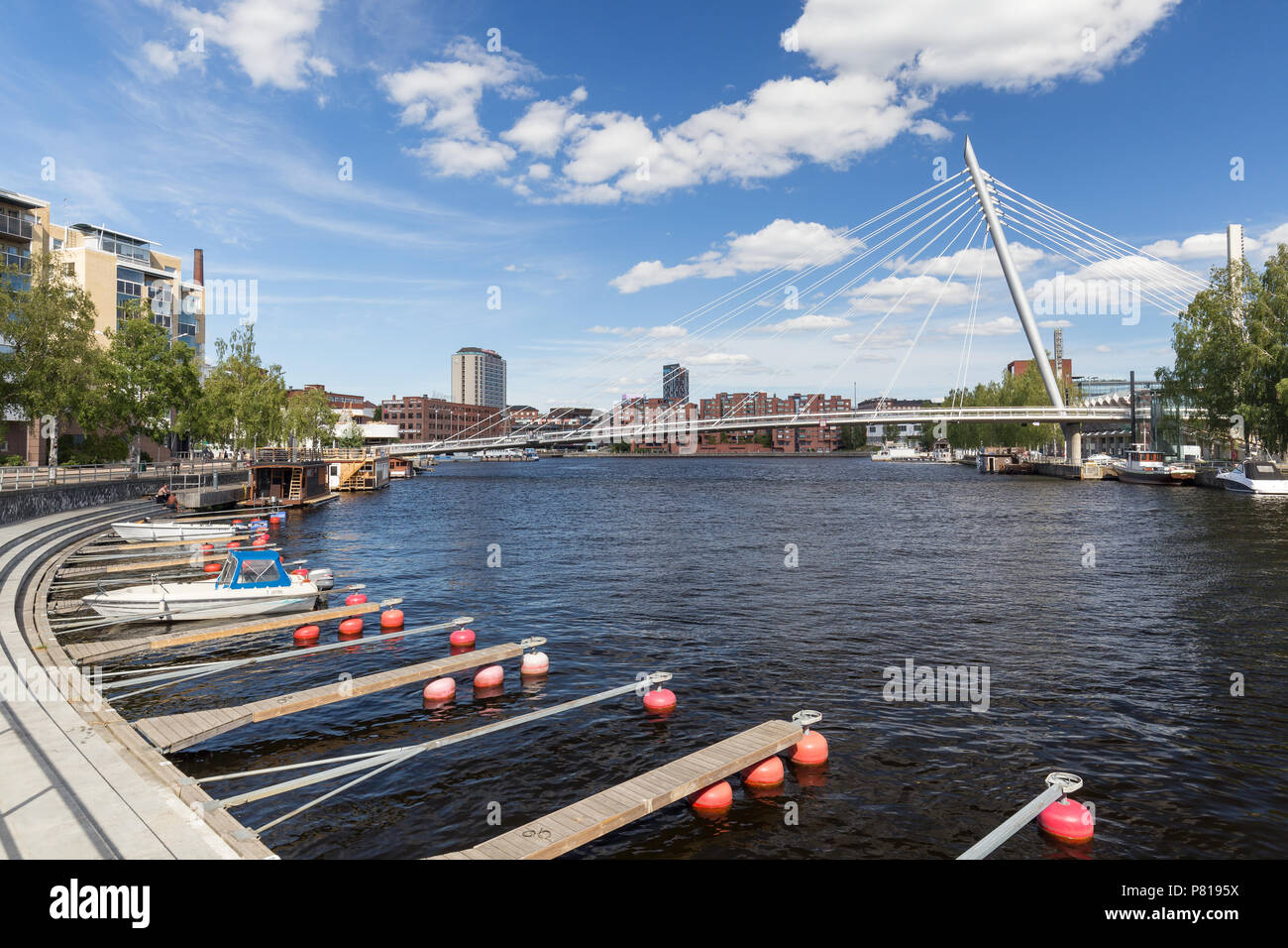 Buildings, bridge and boats at the Ratinan Suvanto (a bay or stream pool between Tammerkoski rapids and Lake Pyhäjärvi) in downtown Tampere, Finland. - Stock Image