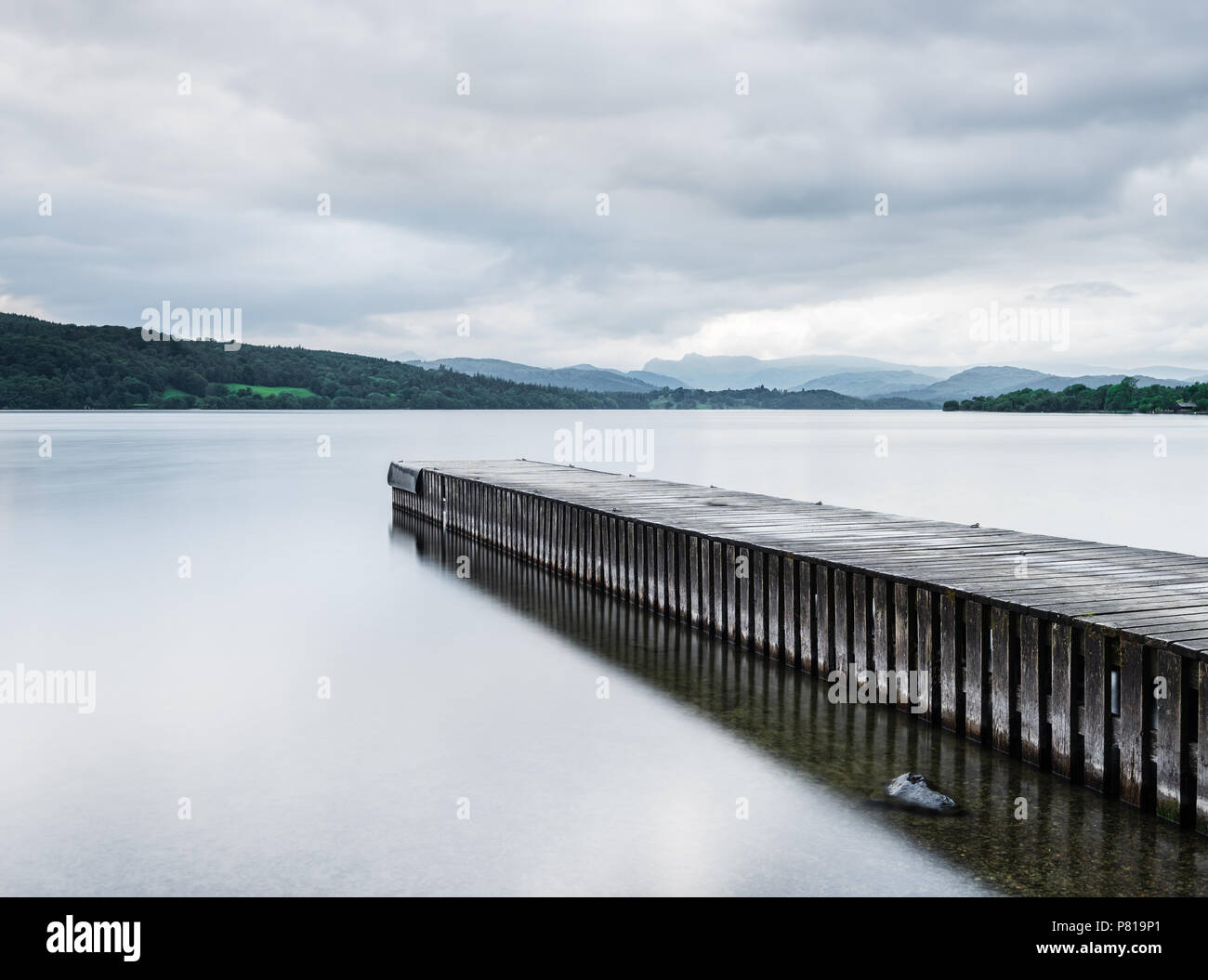 Pier stretching out into the calm waters of Lake Windermere at Miller Ground in the Lake District with the Langdale Pikes in the distance - Stock Image