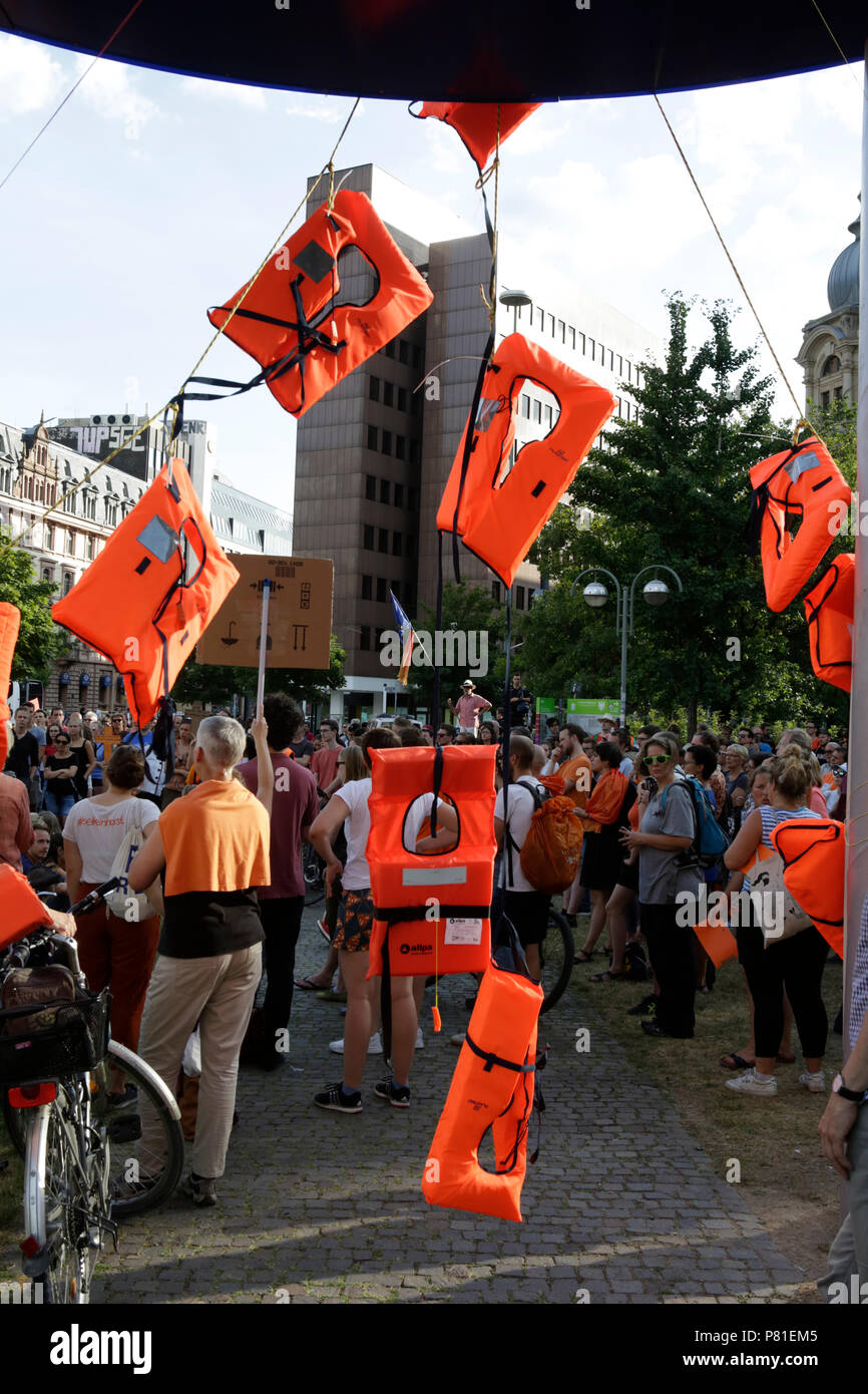 Frankfurt, Germany. 07th July, 2018. Several life jackets hang from the large Euro sign outside the former seat of the ECB. Around 800 protesters marched through Frankfurt to protest against the politics of the German government and the EU of closed borders and the prevention of sea rescue operations of NGOs, by grounding their ships in Malta, that causes refugees to drown in the Mediterranean. They called for the Mayor of Frankfurt to declare Frankfurt a safe haven city for refugees from the Mediterranean. The protest was part of the German wide Seebrucke (Sea bridge) protest that saw thousan Stock Photo