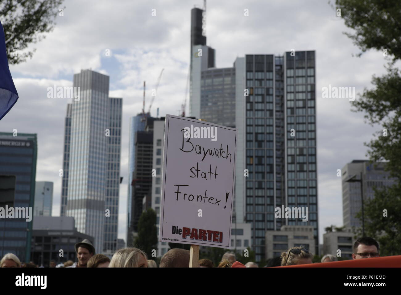 Frankfurt, Germany. 07th July, 2018. A protester holds a sign that reads 'Baywatch instead of Frontex!' with the Frankfurt skyline in the background. Around 800 protesters marched through Frankfurt to protest against the politics of the German government and the EU of closed borders and the prevention of sea rescue operations of NGOs, by grounding their ships in Malta, that causes refugees to drown in the Mediterranean. They called for the Mayor of Frankfurt to declare Frankfurt a safe haven city for refugees from the Mediterranean. The protest was part of the German wide Seebrucke (Sea bridge Stock Photo