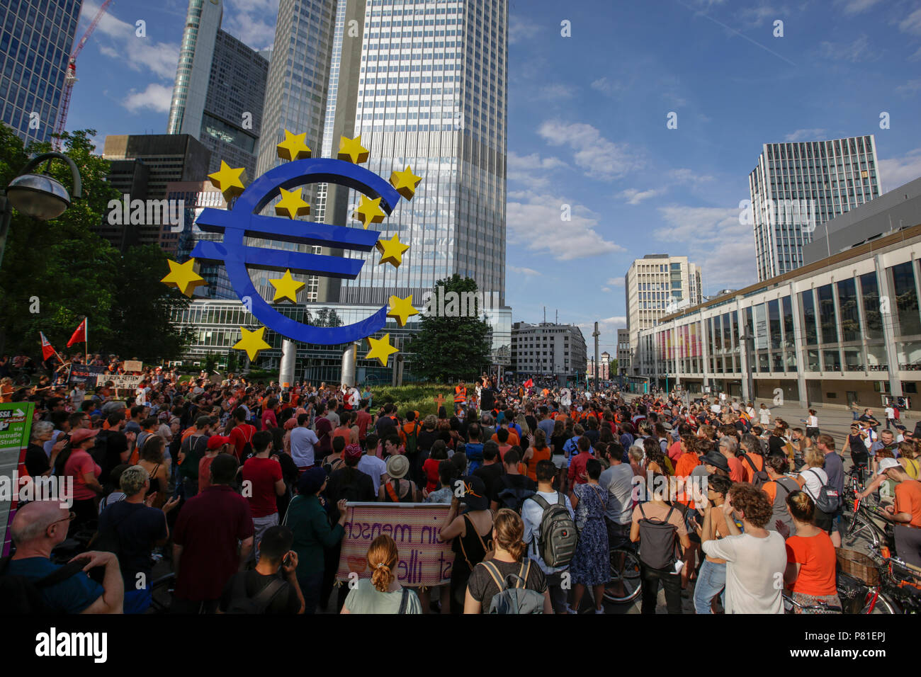 Frankfurt, Germany. 07th July, 2018. Protesters have assembled at the large Euro sign outside the former seat of the ECB. Around 800 protesters marched through Frankfurt to protest against the politics of the German government and the EU of closed borders and the prevention of sea rescue operations of NGOs, by grounding their ships in Malta, that causes refugees to drown in the Mediterranean. They called for the Mayor of Frankfurt to declare Frankfurt a safe haven city for refugees from the Mediterranean. The protest was part of the German wide Seebrucke (Sea bridge) protest that saw thousands Stock Photo
