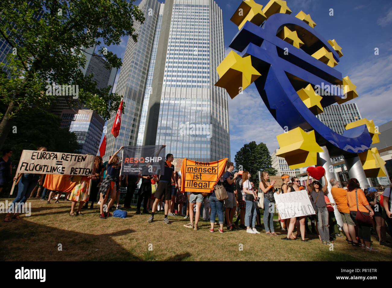 Frankfurt, Germany. 07th July, 2018. Protesters pose with banners and signs at the large Euro sign outside the former seat of the ECB. Around 800 protesters marched through Frankfurt to protest against the politics of the German government and the EU of closed borders and the prevention of sea rescue operations of NGOs, by grounding their ships in Malta, that causes refugees to drown in the Mediterranean. They called for the Mayor of Frankfurt to declare Frankfurt a safe haven city for refugees from the Mediterranean. The protest was part of the German wide Seebrucke (Sea bridge) protest that  Stock Photo