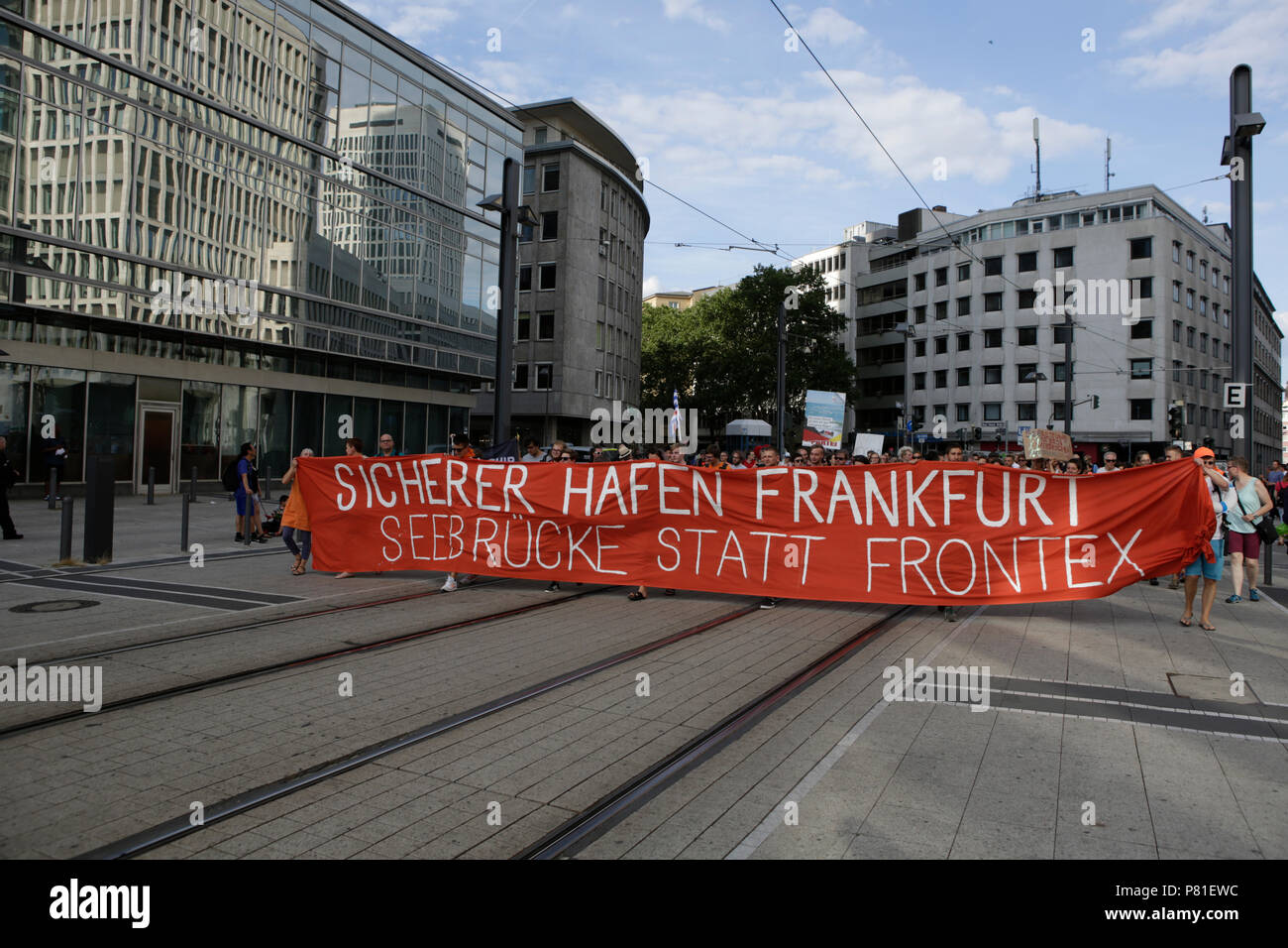 Frankfurt, Germany. 07th July, 2018. Protesters carry a banner that reads 'Safe haven Frankfurt - Seebrucke (Sea bridge) instead of FRONTEX' through Frankfurt. Around 800 protesters marched through Frankfurt to protest against the politics of the German government and the EU of closed borders and the prevention of sea rescue operations of NGOs, by grounding their ships in Malta, that causes refugees to drown in the Mediterranean. They called for the Mayor of Frankfurt to declare Frankfurt a safe haven city for refugees from the Mediterranean. The protest was part of the German wide Seebrucke ( Stock Photo