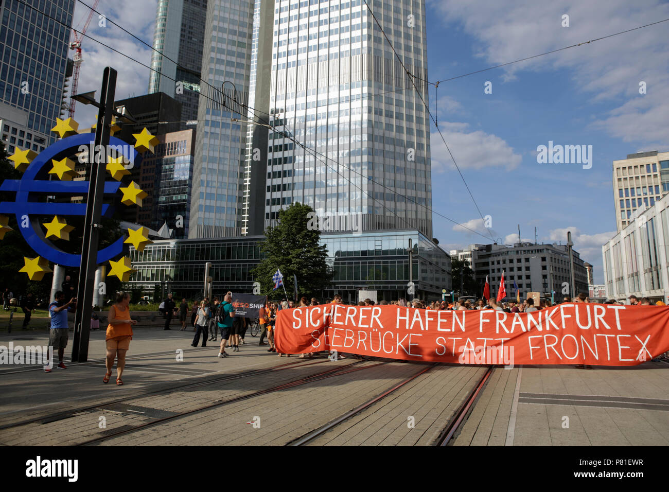 Frankfurt, Germany. 07th July, 2018. Protesters stand with a banner that reads 'Safe haven Frankfurt - Seebrucke (Sea bridge) instead of FRONTEX' in front of the Euro sign outside the former seat of the ECB. Around 800 protesters marched through Frankfurt to protest against the politics of the German government and the EU of closed borders and the prevention of sea rescue operations of NGOs, by grounding their ships in Malta, that causes refugees to drown in the Mediterranean. They called for the Mayor of Frankfurt to declare Frankfurt a safe haven city for refugees from the Mediterranean. The Stock Photo