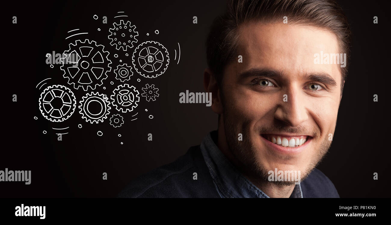 Portrait of a young businessman with rotating gears next to him on a dark background - Stock Image