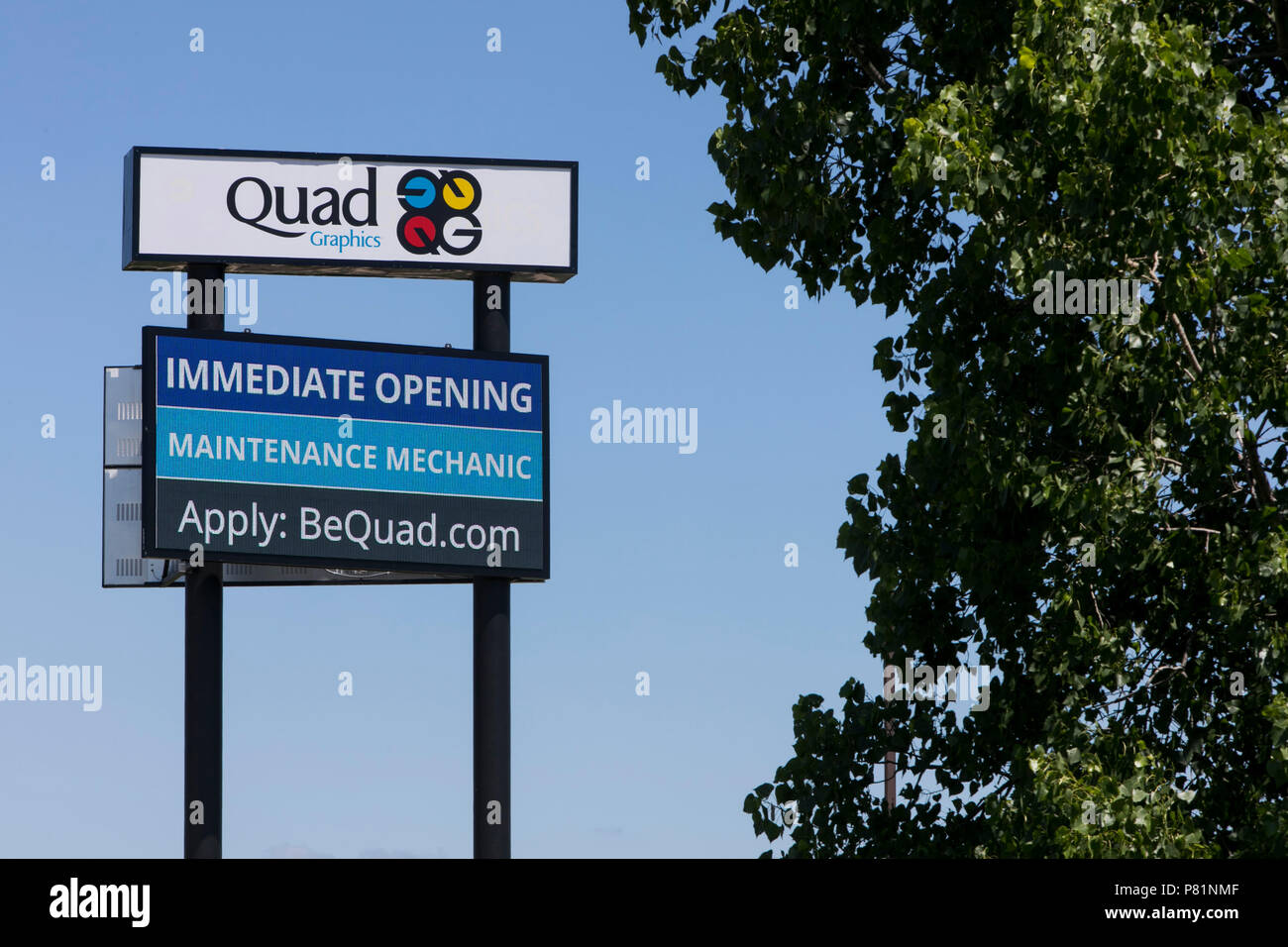 A logo sign outside of a facility occupied by Quad/Graphics in Lomira, Wisconsin, on June 24, 2018. - Stock Image
