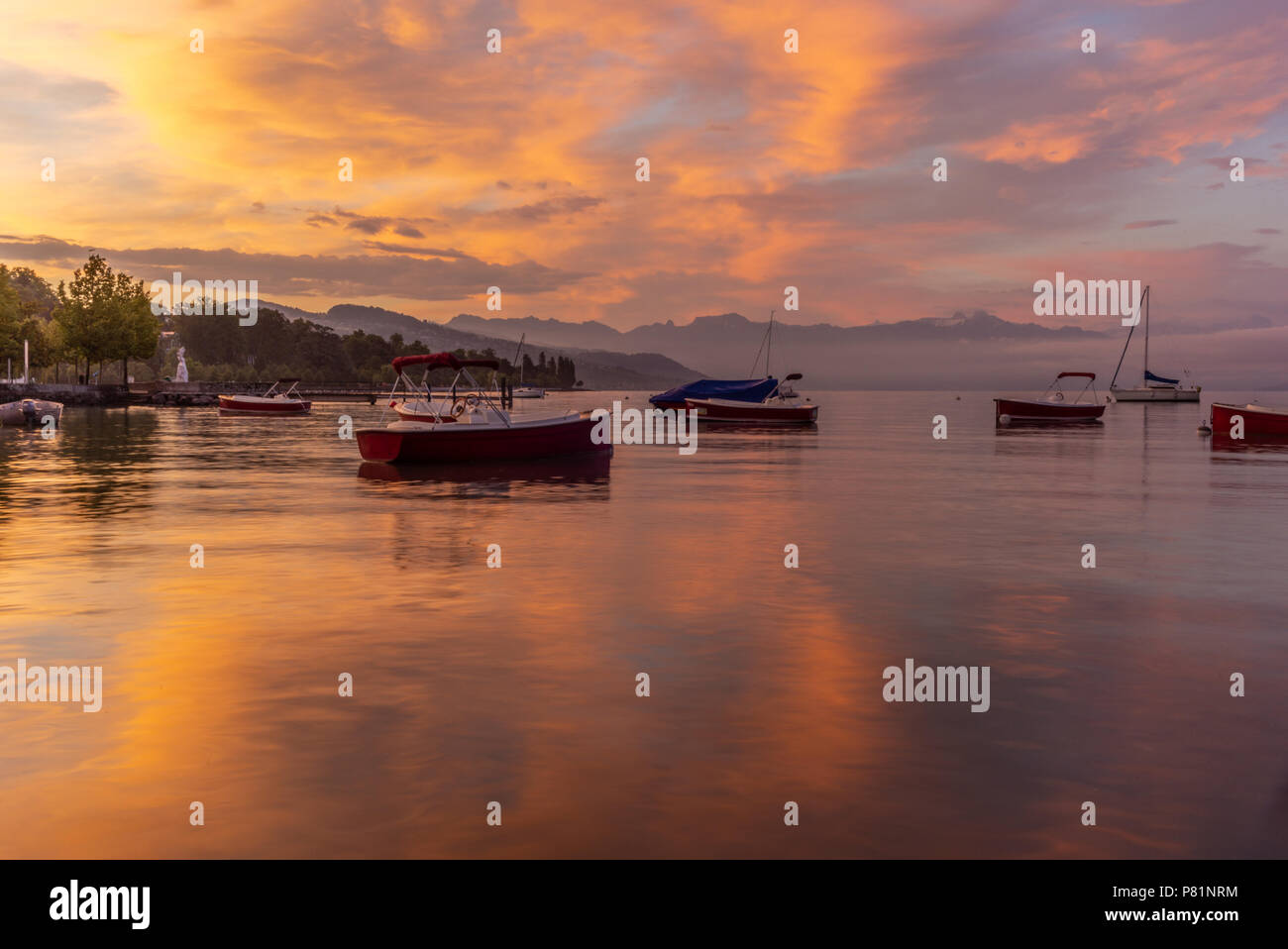 Colorful sunrise on the marina of Lausanne on the Lake Leman in summer with the view of the Swiss Alps in background - 6 - Stock Image