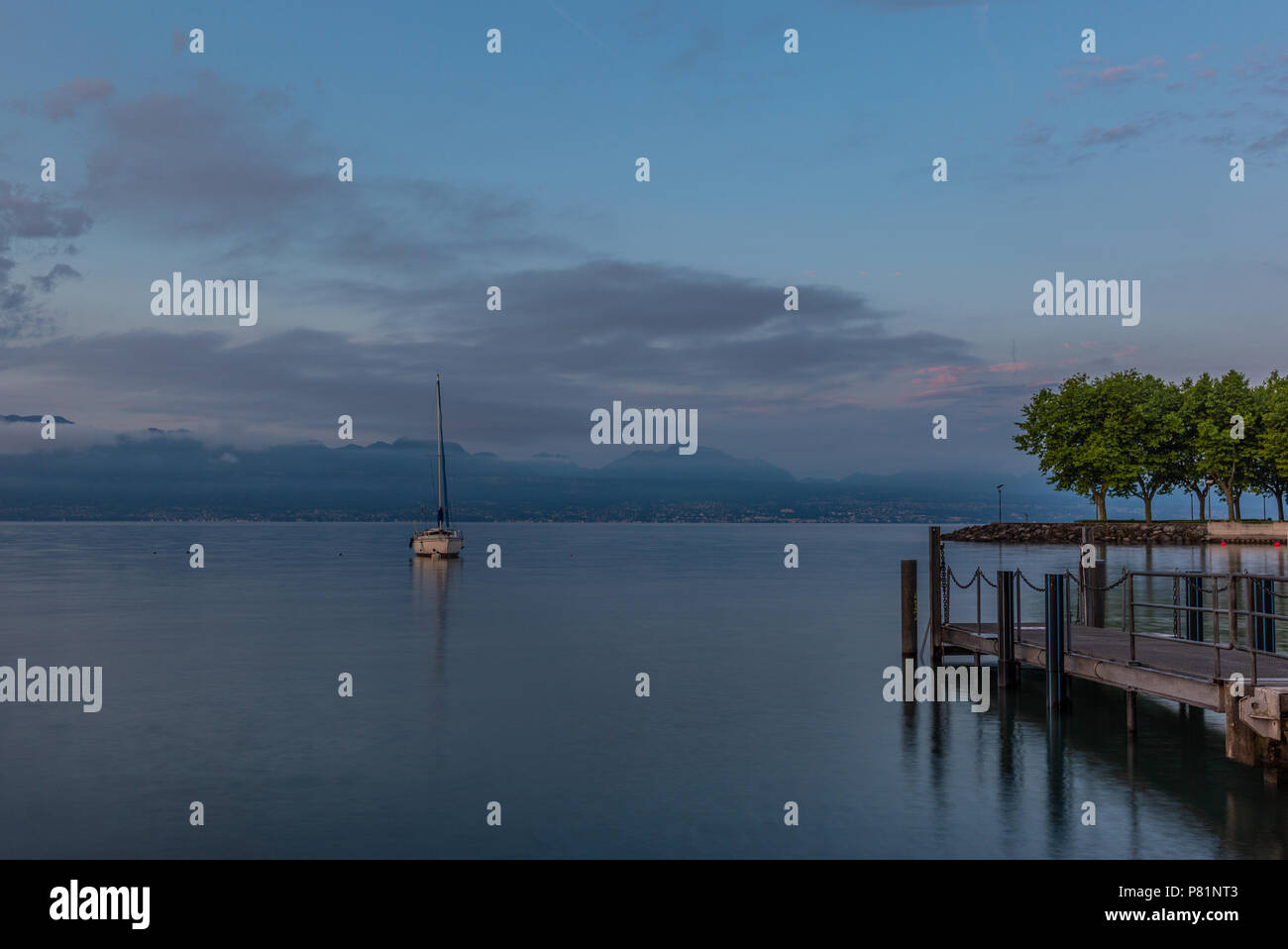 Colorful sunrise on the marina of Lausanne on the Lake Leman in summer with the view of the Swiss Alps in background - 14 - Stock Image