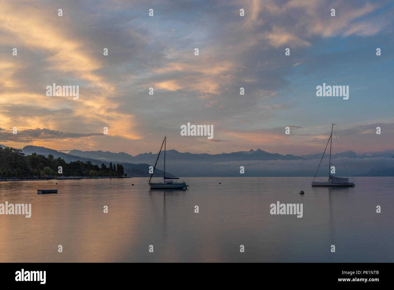 Colorful sunrise on the marina of Lausanne on the Lake Leman in summer with the view of the Swiss Alps in background - 21 - Stock Image