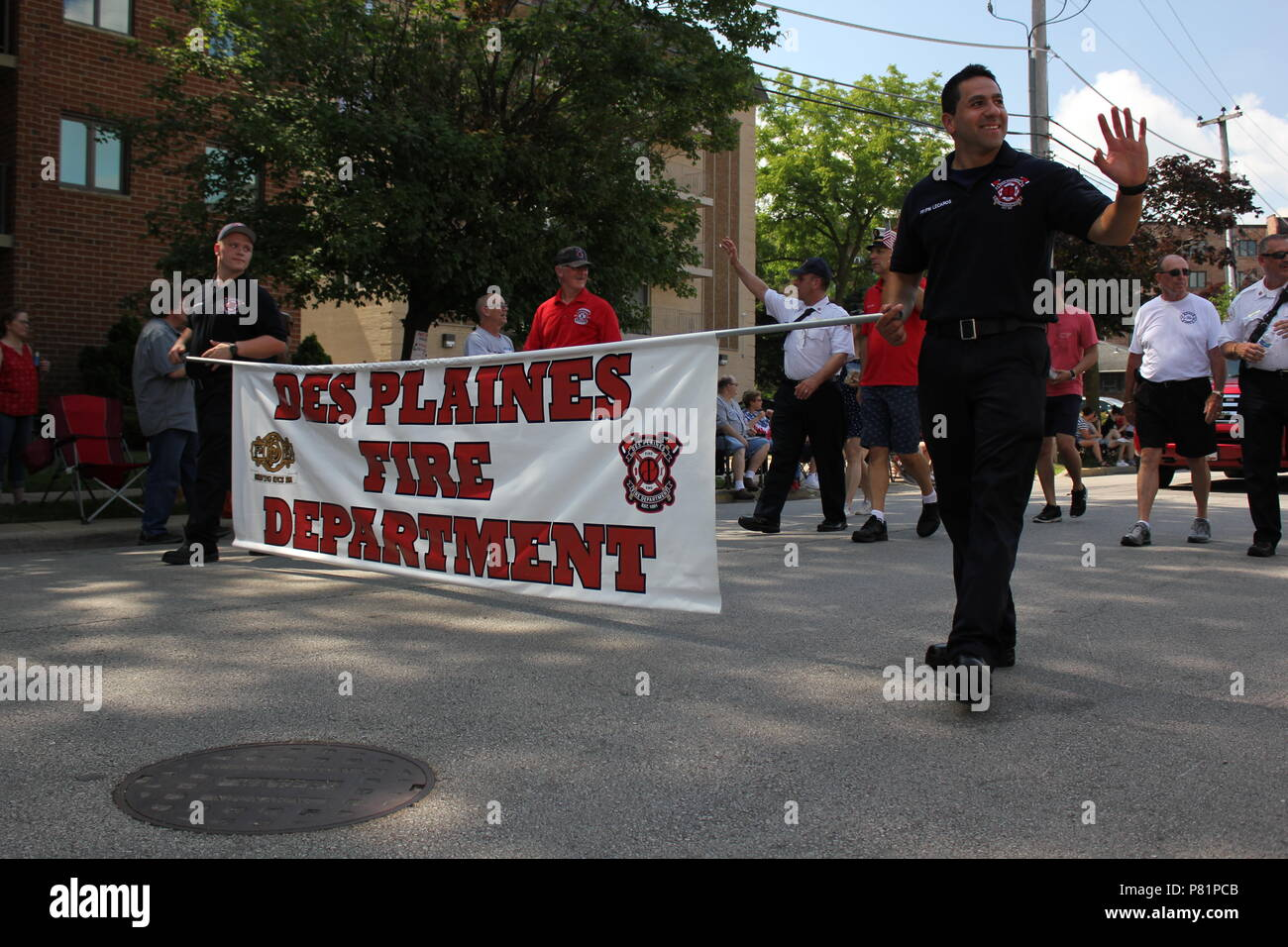 Des Plaines Fire Department parading in the Fourth of July Parade in Des Plaines, Illinois. - Stock Image