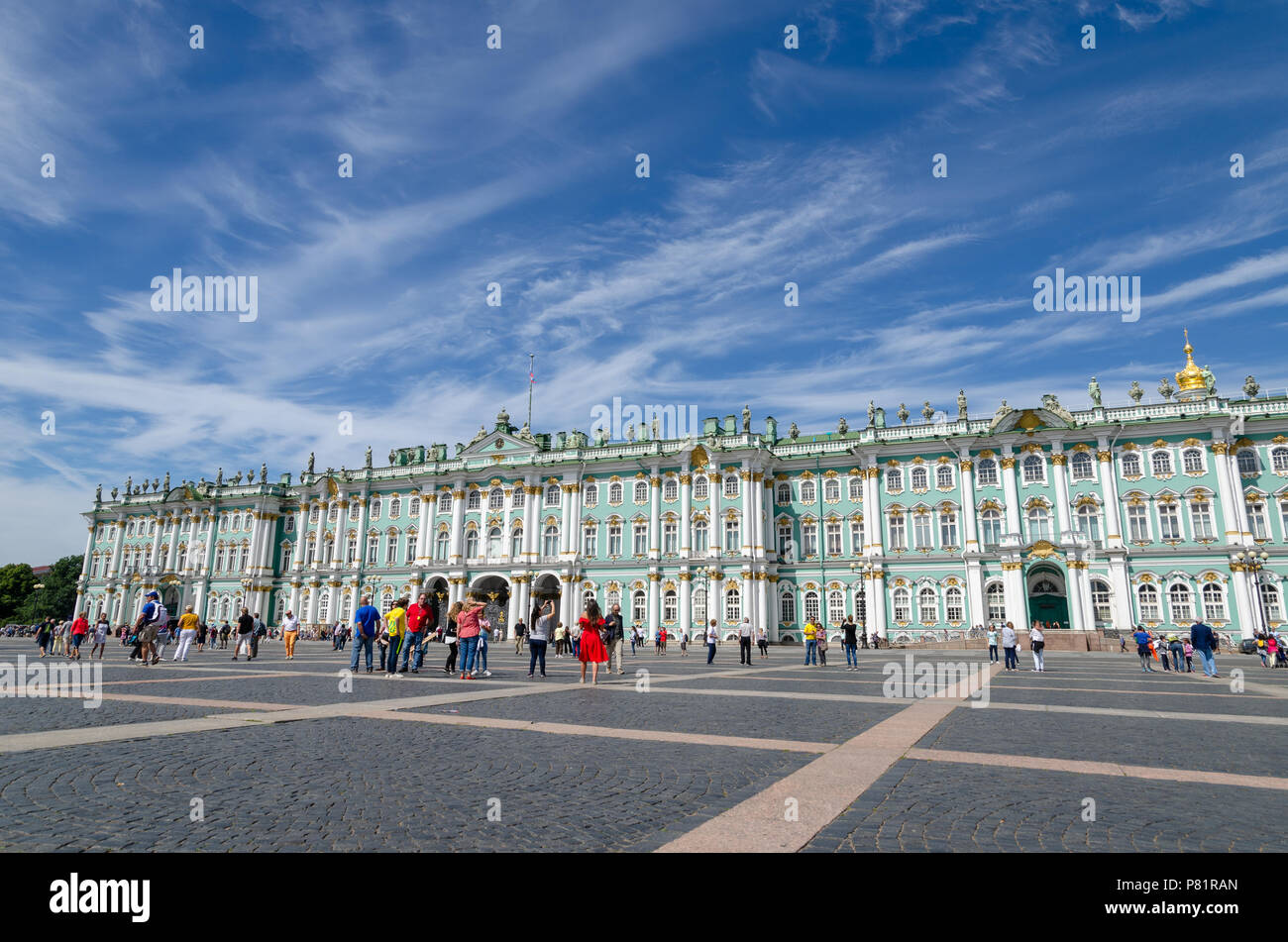 Tourists sightseeing at the Winter Palace from the Palace Square in St Petersburg - Stock Image