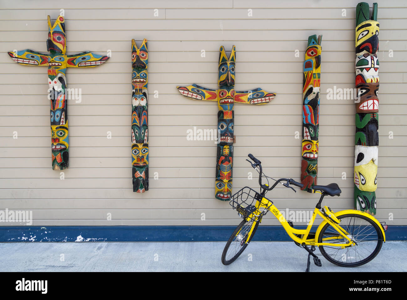 Native wooden painted totems hanging on a wall of the Pier 54 with a yellow bike for rent parked on the sidewalk, Seattle waterfront, WA, USA. - Stock Image
