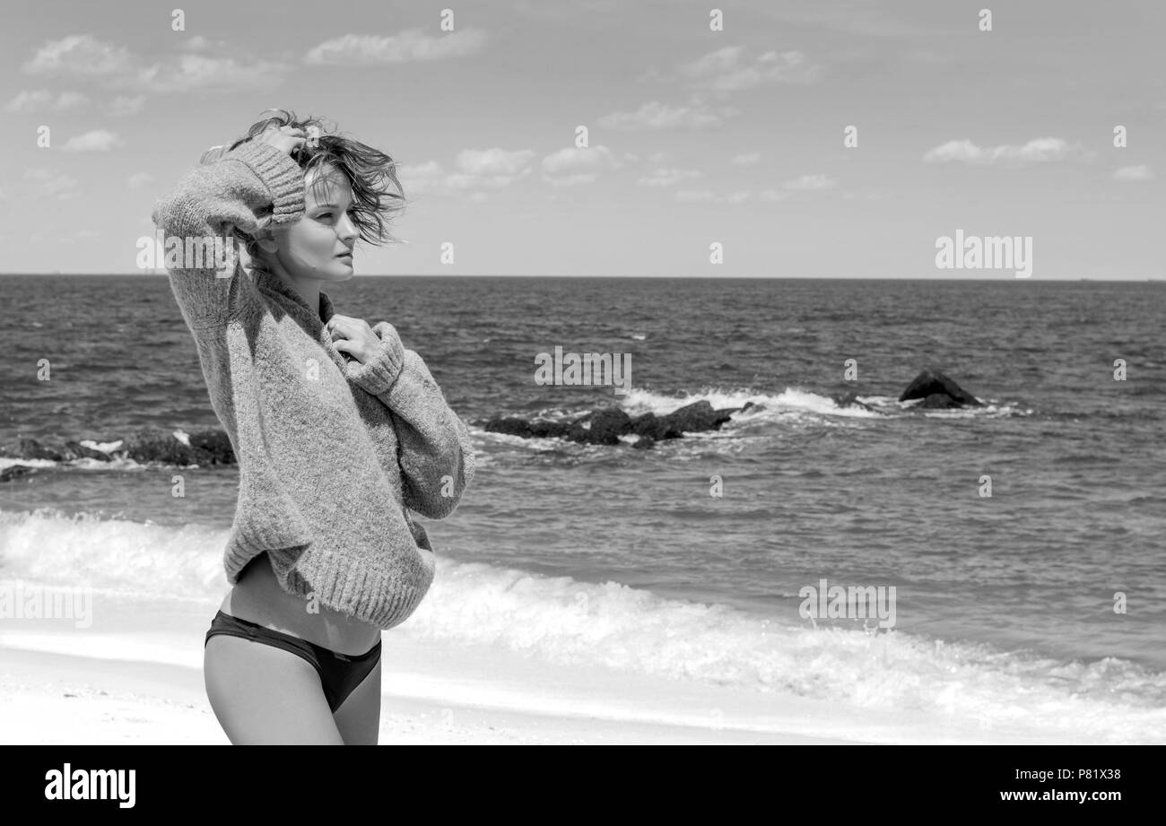 Happy tanned woman in bikini enjoying a walk by the sea on tropical beach - Stock Image
