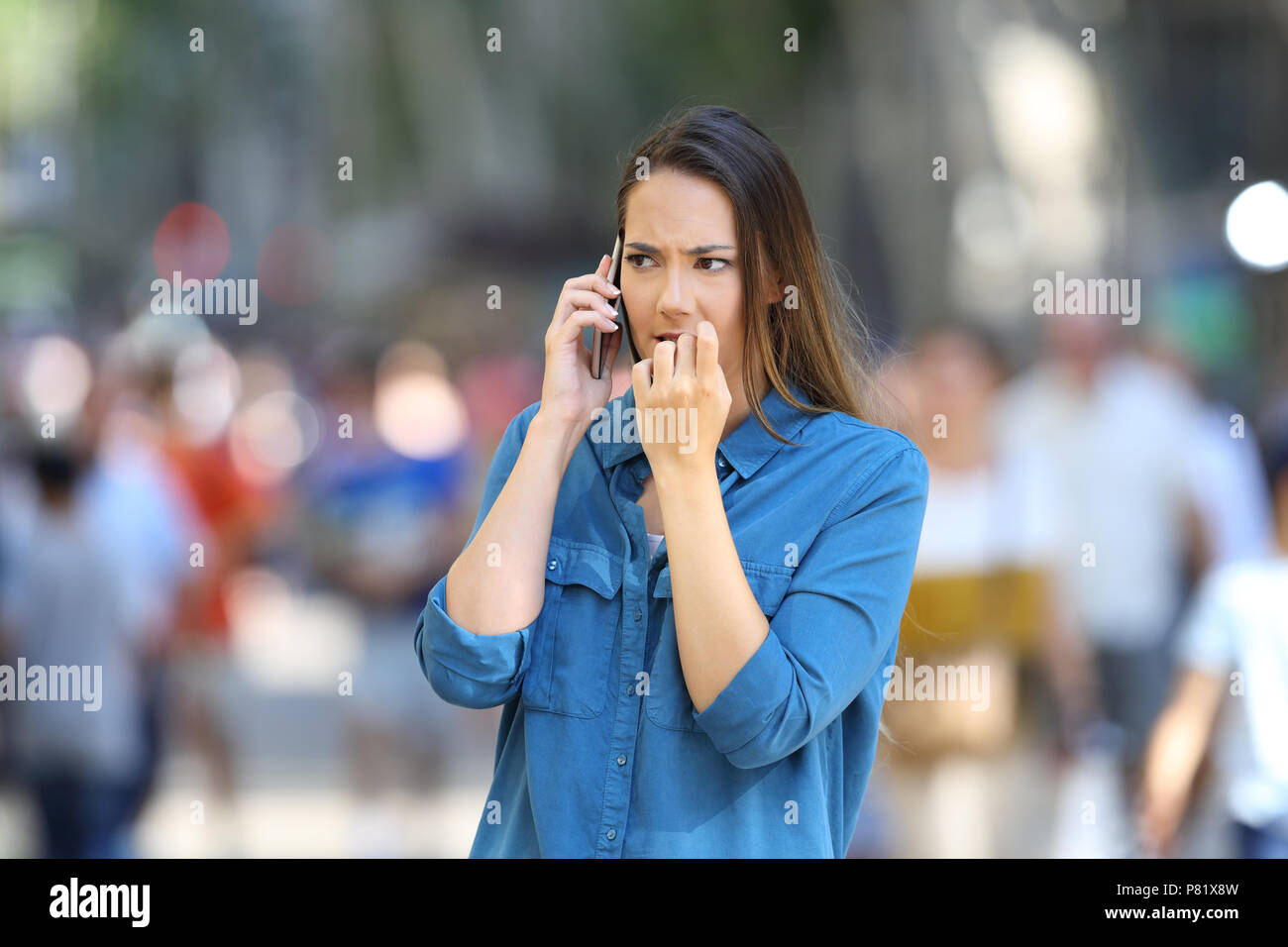 Nervous woman biting nails while is talking on phone on the street - Stock Image
