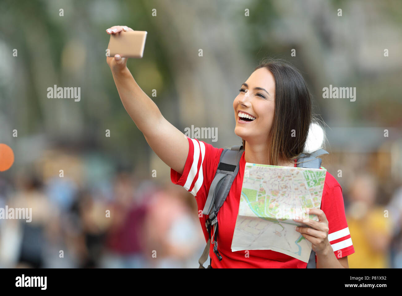 Happy teen tourist taking selfie in the street holding a map - Stock Image