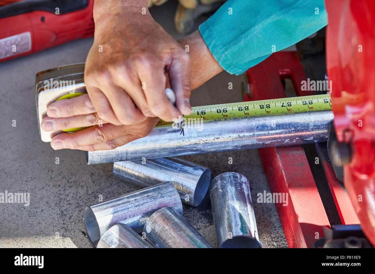 A construction worker marking the measurement on a galvanized steel pipe in preparation to cut it with a chop saw - Stock Image