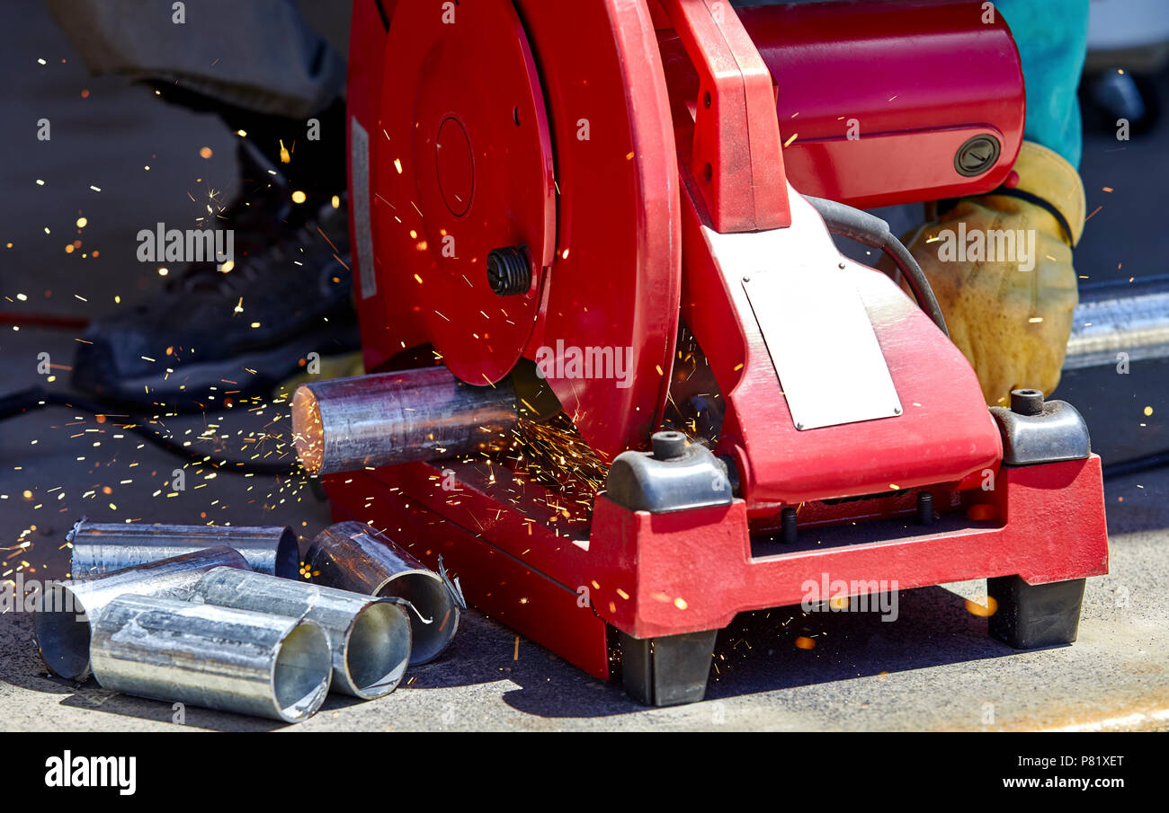 A construction worker cutting a galvanized steel pipe with a chop saw chop saw - Stock Image