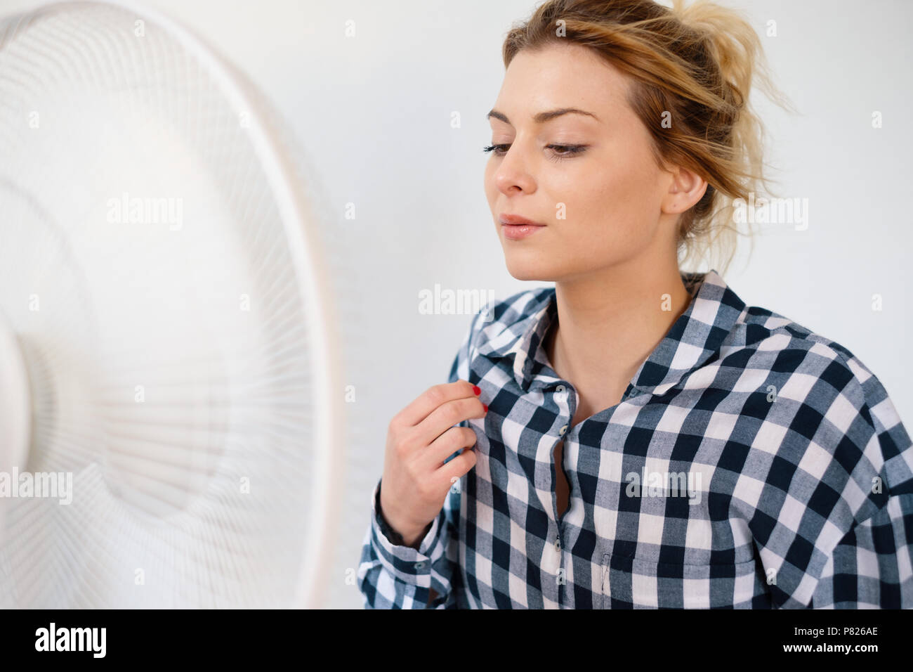 Girl face expression cooling in front of a fan - Stock Image