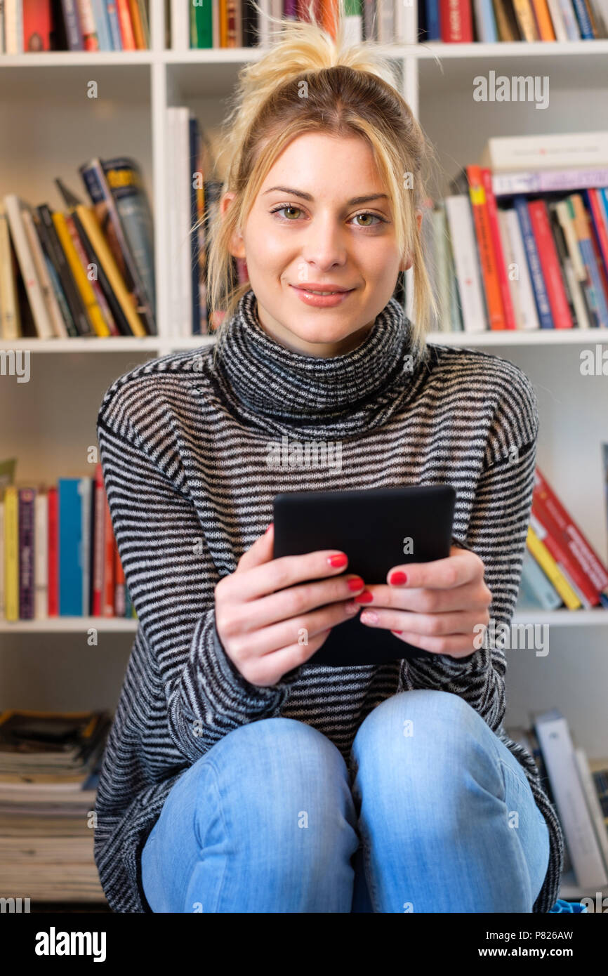 Young girl reading e-book reader next to colorful bookshelf - Stock Image