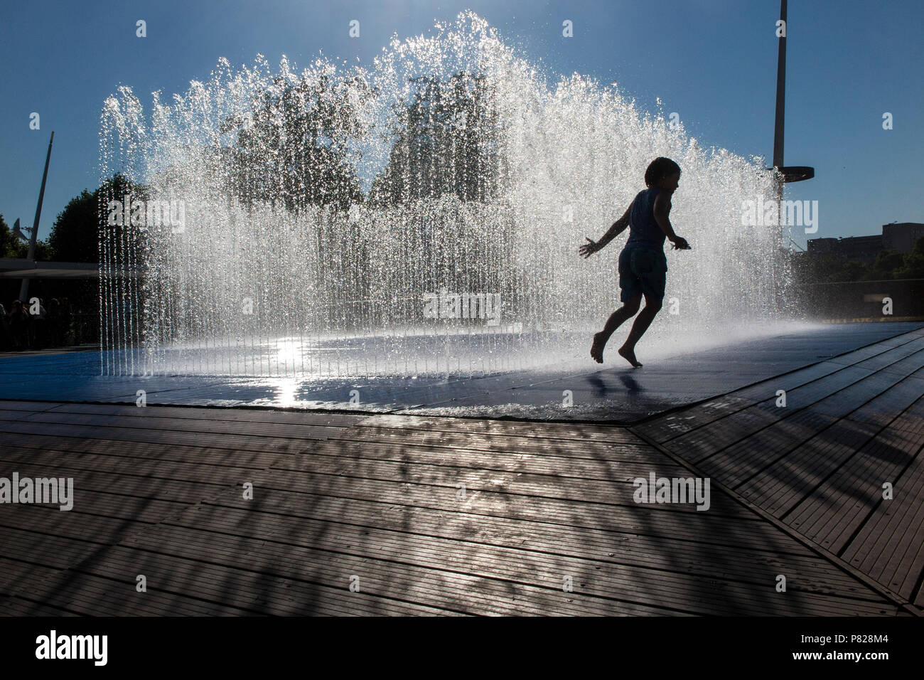 Children play in the fountains on London's Southbank Centre on a hot summer's day as England enjoys a heatwave - Stock Image