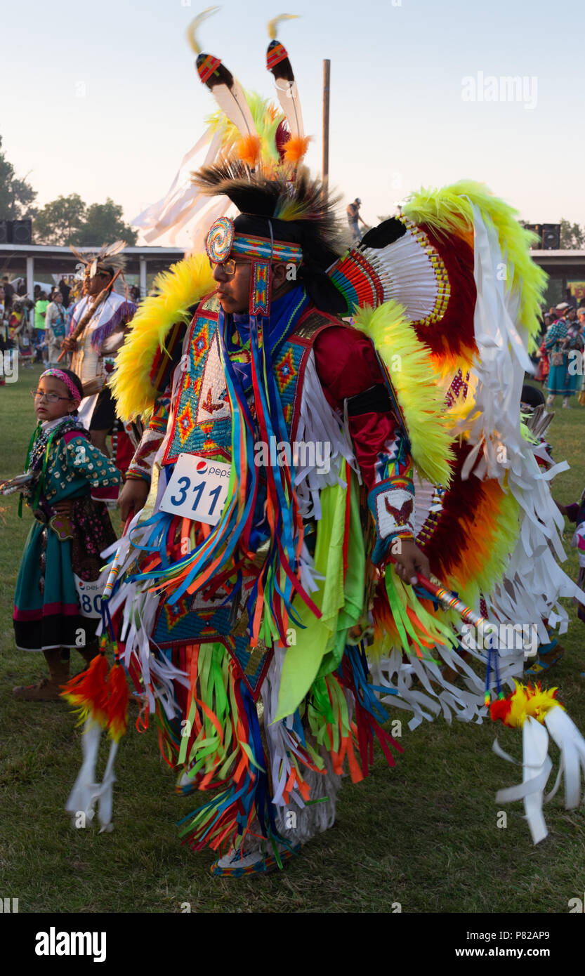A Native American Dancing in Neon Yellow, Green and Orange Ceremonial Costume at a Pow Wow. A little girl is dancing in the background. Photographed a - Stock Image