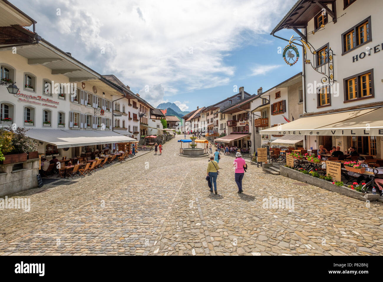Rue de Bourg, the medieval road up to the Gruyeres Casltle. Nice restaurants and happy people. - Stock Image