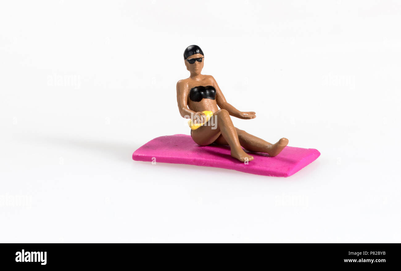 Miniature lady applying sun cream while sunbathing on a pink towel at the seaside on summer vacation isolated on white with copy space - Stock Image