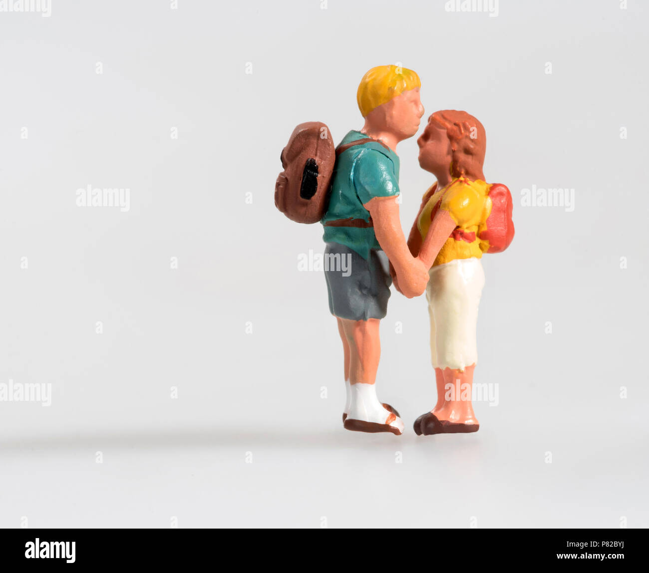 Miniature young couple in love wearing backpacks standing facing each other holding hands isolated on white with copy space in a show of affection Stock Photo