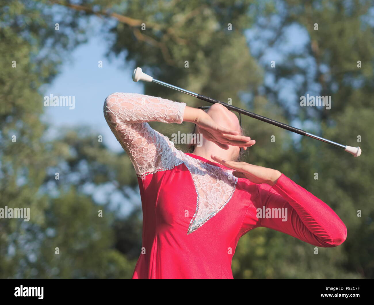 Bespectacled Blonde Teen Majorette Girl Twirling Baton Outdoors in Red Dress - Stock Image