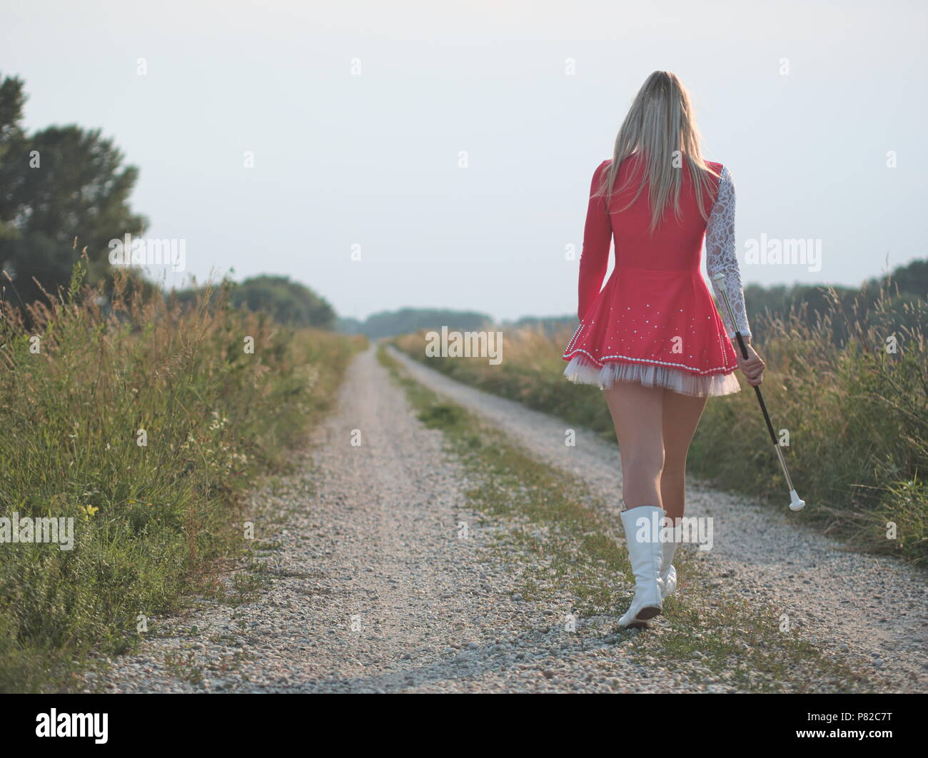 Blonde Teen Majorette Girl Twirling Baton Outdoors in Red Dress - Stock Image