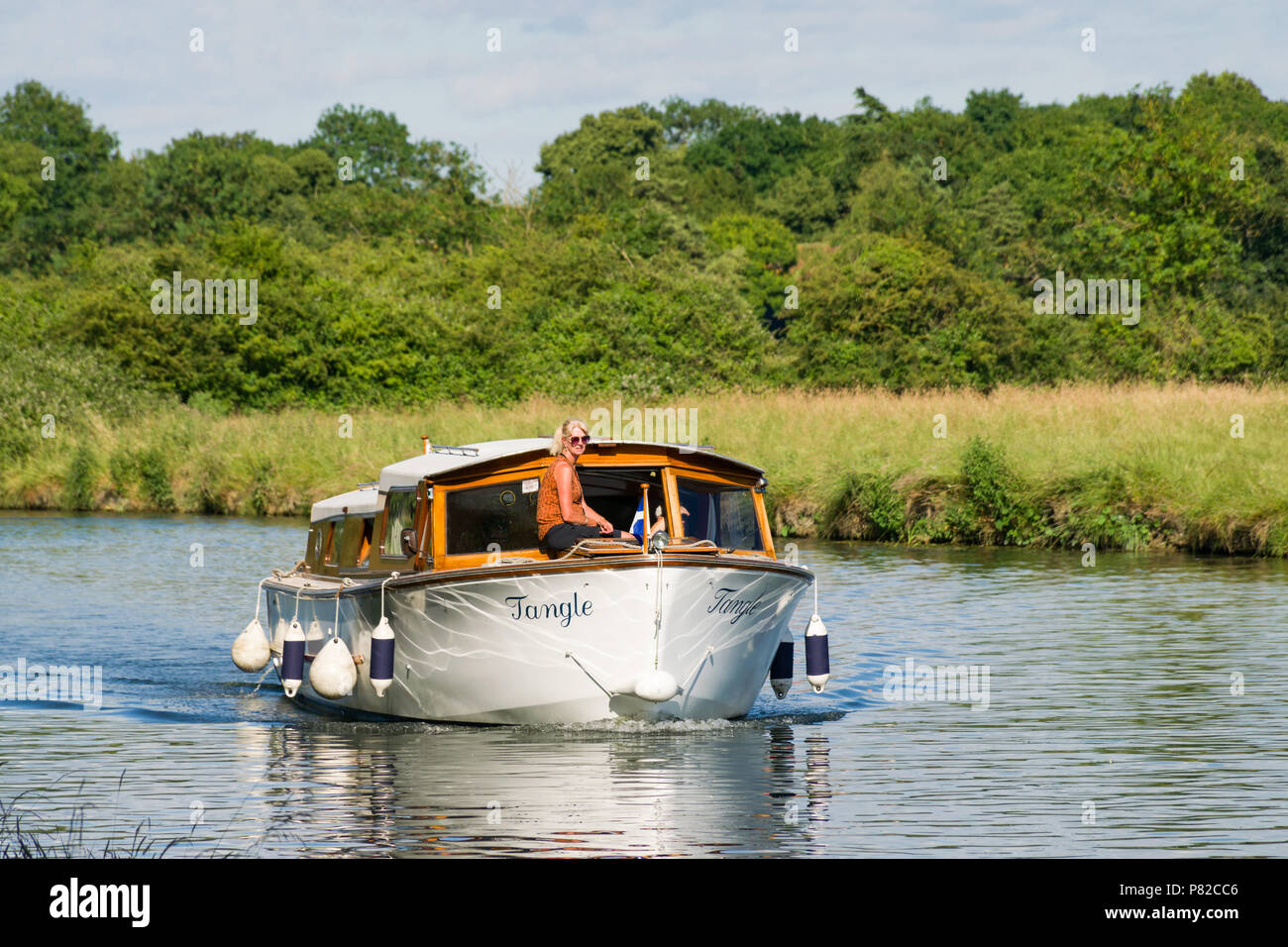 A GRP cruiser cruising on the river Cam with a woman sat on the front on a sunny Summer day, Cambridge - Stock Image