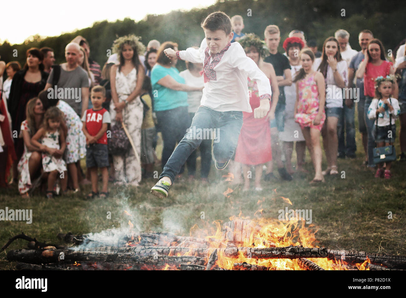 KYIV, UKRAINE - JULY 6, 2018: Young boy jumps over the flames of bonfire during the traditional Slavic celebration of Ivana Kupala holiday in Pirogovo - Stock Image