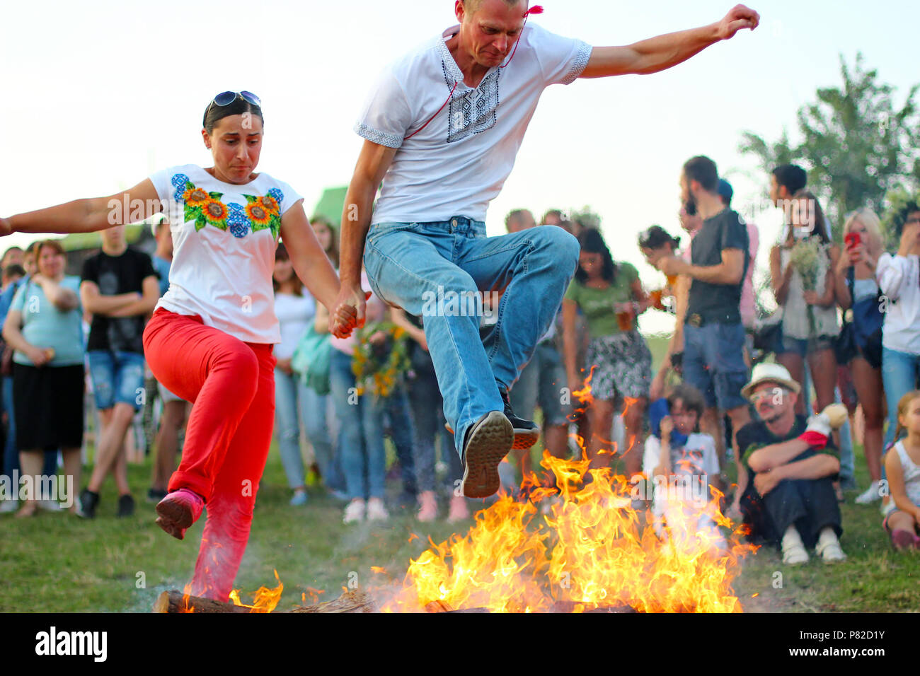 KYIV, UKRAINE - JULY 6, 2018: People jump over the flames of bonfire during the traditional Slavic celebration of Ivana Kupala holiday in Pirogovo ope - Stock Image