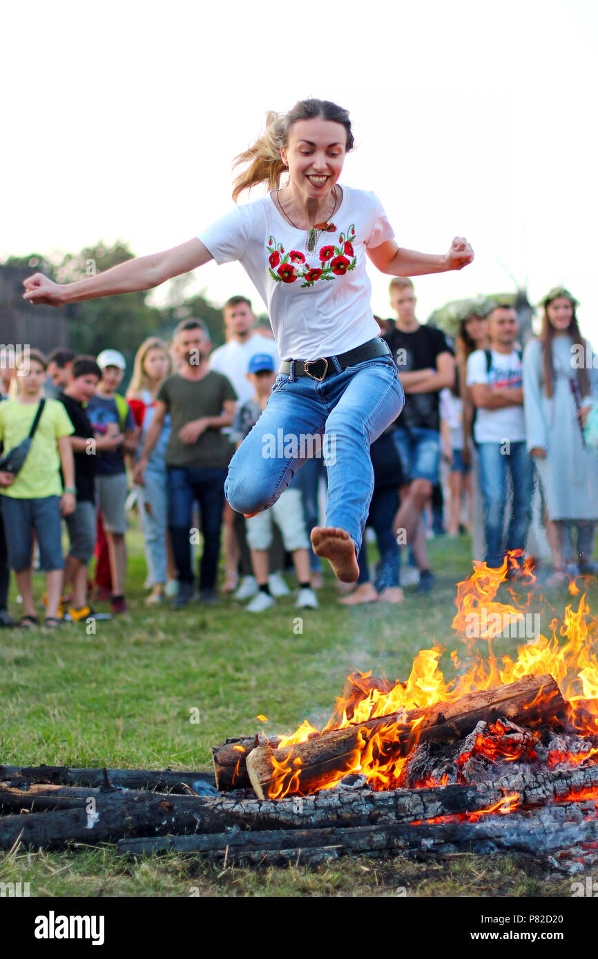 KYIV, UKRAINE - JULY 6, 2018: Young people jump over the flames of bonfire during the traditional Slavic celebration of Ivana Kupala holiday in Pirogo - Stock Image