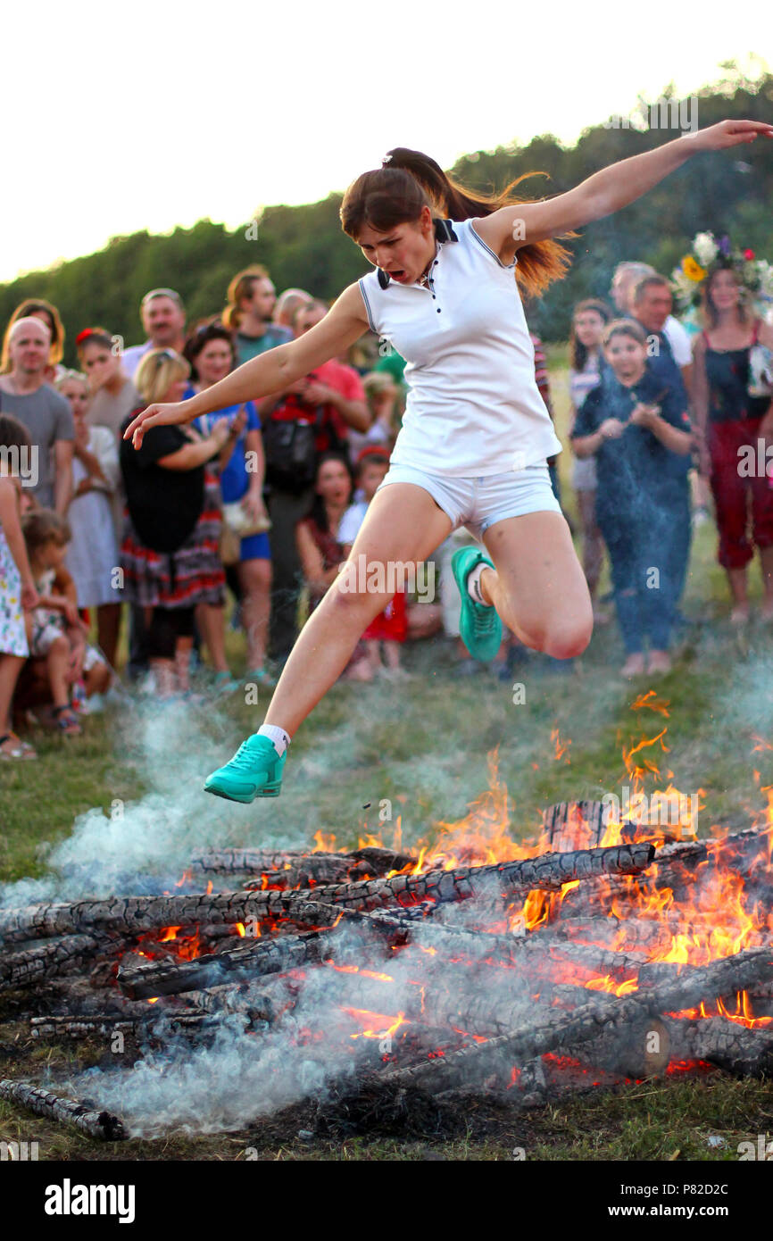 KYIV, UKRAINE - JULY 6, 2018: Young woman jumps over the flames of bonfire during the traditional Slavic celebration of Ivana Kupala holiday in Pirogo - Stock Image