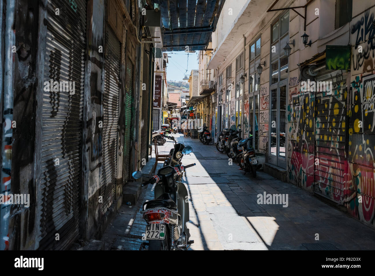 Motorcycles in shadowy tiled street of Athens, Greece. With graffiti on the walls and roller shutters. - Stock Image