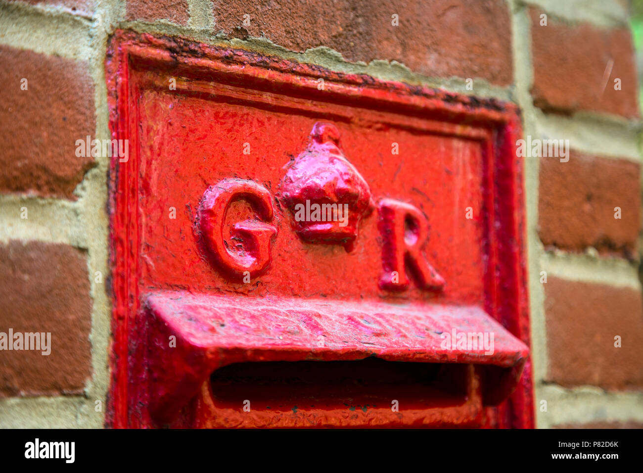 Royal cypher on a red English post box from the time of King George V, Lewes, UK Stock Photo