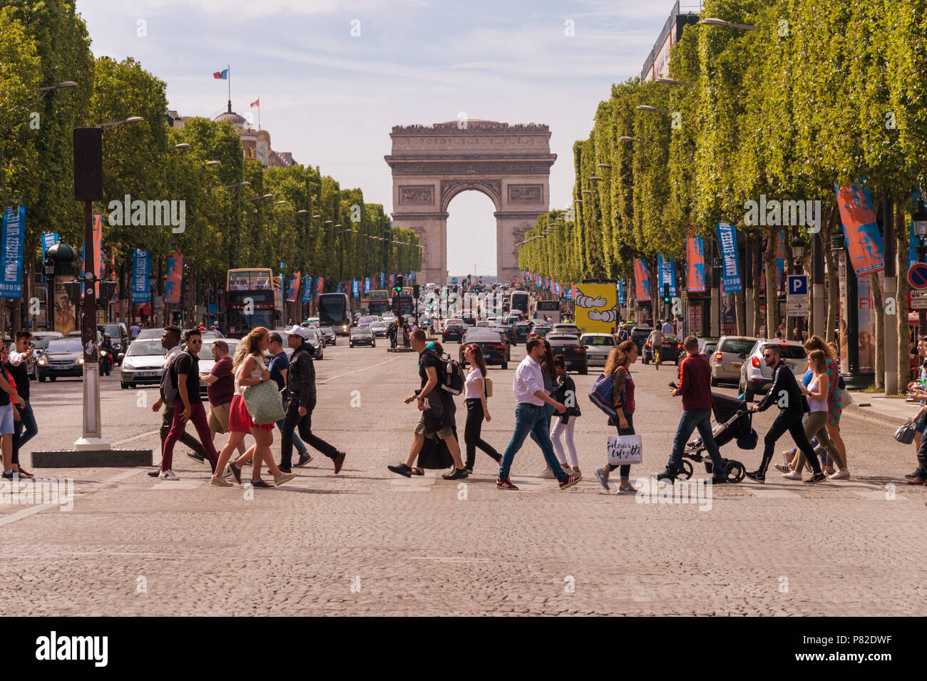 Paris, France - 23 June 2018: A crowd of people crossing Avenue des Champs-Elysees with Arc de Triomphe in the Background - Stock Image