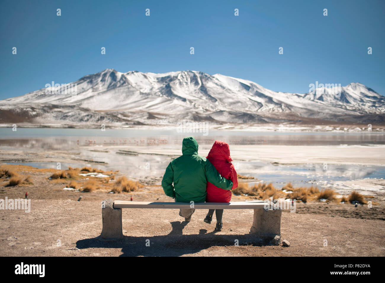 Couple watching the amazing panorama of Laguna Cañapa (Cañapa salt lake) in the Potosí Department, Bolivia. - Stock Image