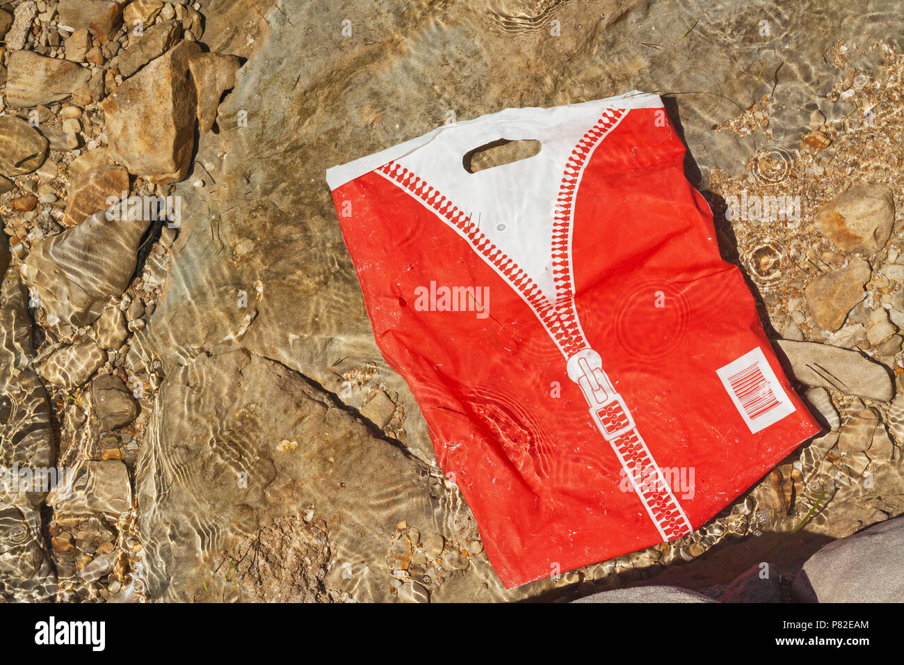 Waste plastic bag floating in clean water close to coast. - Stock Image