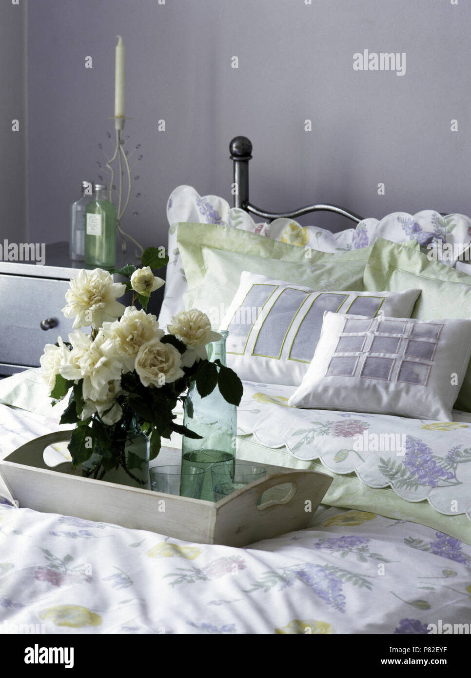 Vase of white roses on a wooden chair on a bed with applique ...