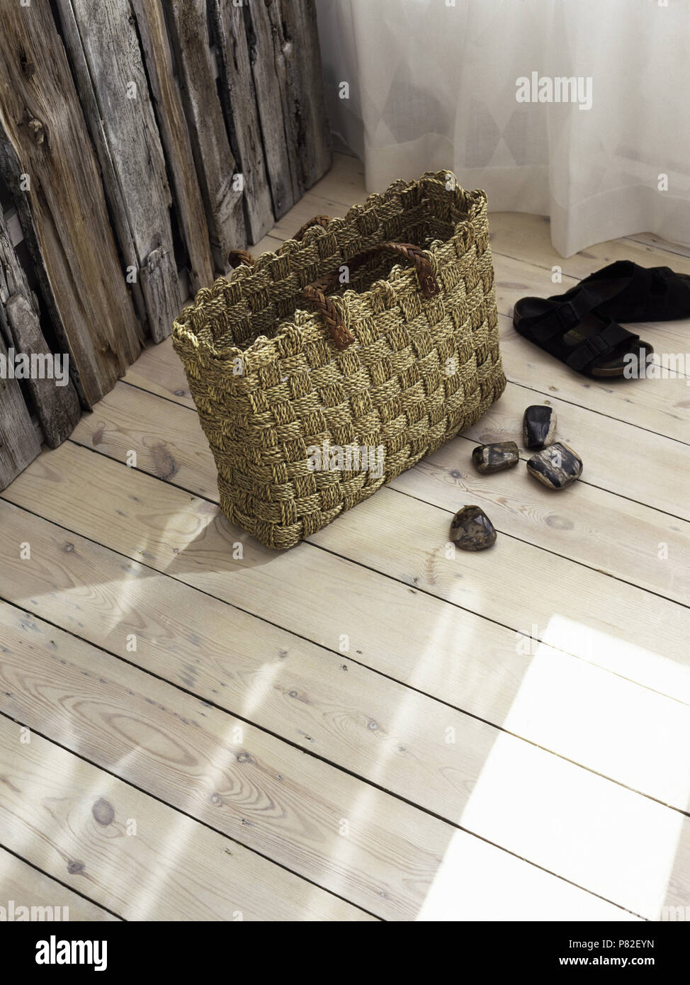 Woven sisal basket on newly fitted pale wood floorboards beside rustic wooden panelling Stock Photo