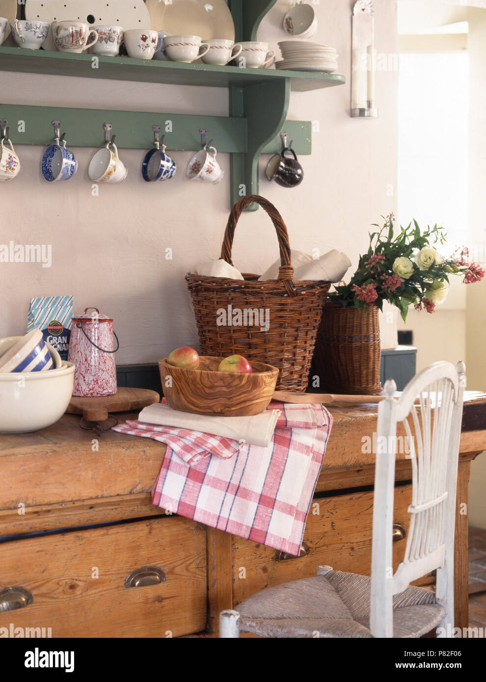 Wicker Basket On An Old Pine Dresser Below Green Painted Wall Shelves With Vintage China Cups Stock Photo Alamy