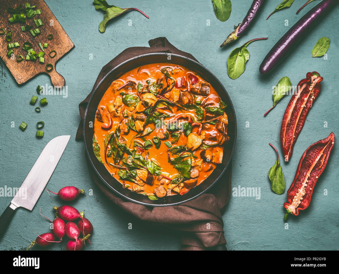Vegetables chicken pan with curry sauce on kitchen table background with ingredients, top view, flat lay. Healthy dieting food and eating concept - Stock Image