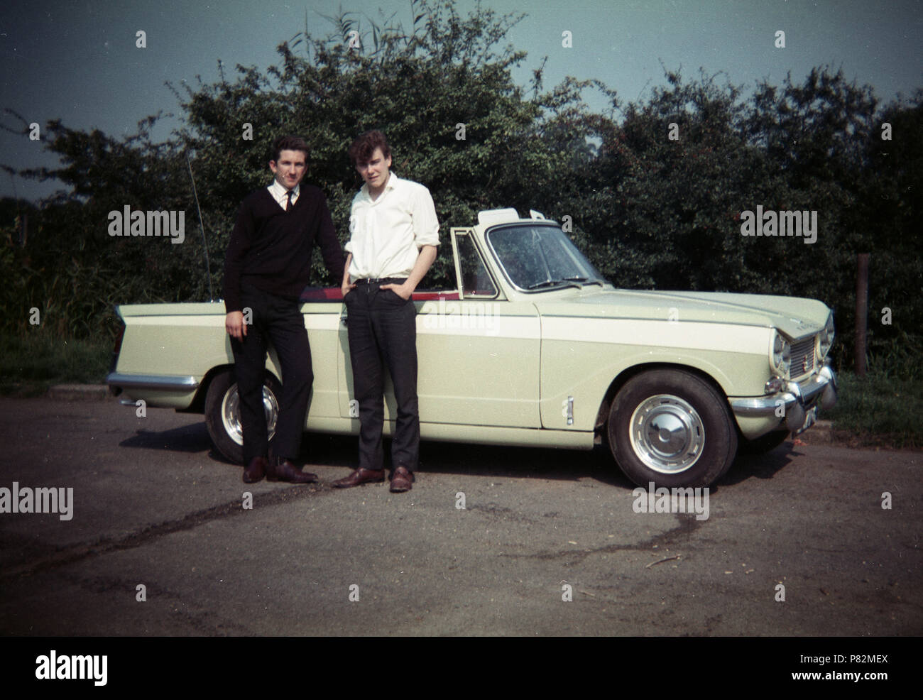 Late 1960s, two young men standing by a British made car, a Triumph Herald 13/60 convertible motorcar, england, UK, made by the Standard-Triumph Co of Coventry. This version, the drop-head, was considered the most attractive but by this time, the 1300 cc engine was under-powered compared to others. - Stock Image