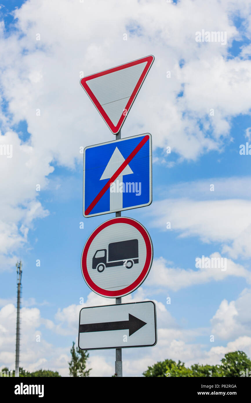 give way, Yield Sign, the passage is forbidden for trucks, the end of one-way traffic and turn right the road signs - Stock Image