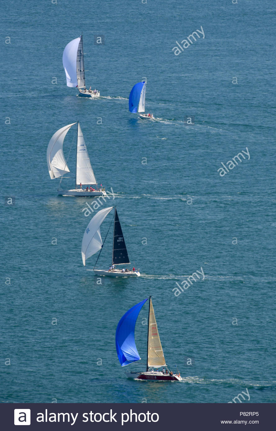 Racing yachts taking part in the annual Round the Island Race off the coast of the Isle of Wight on a hot summers day with very little wind. - Stock Image