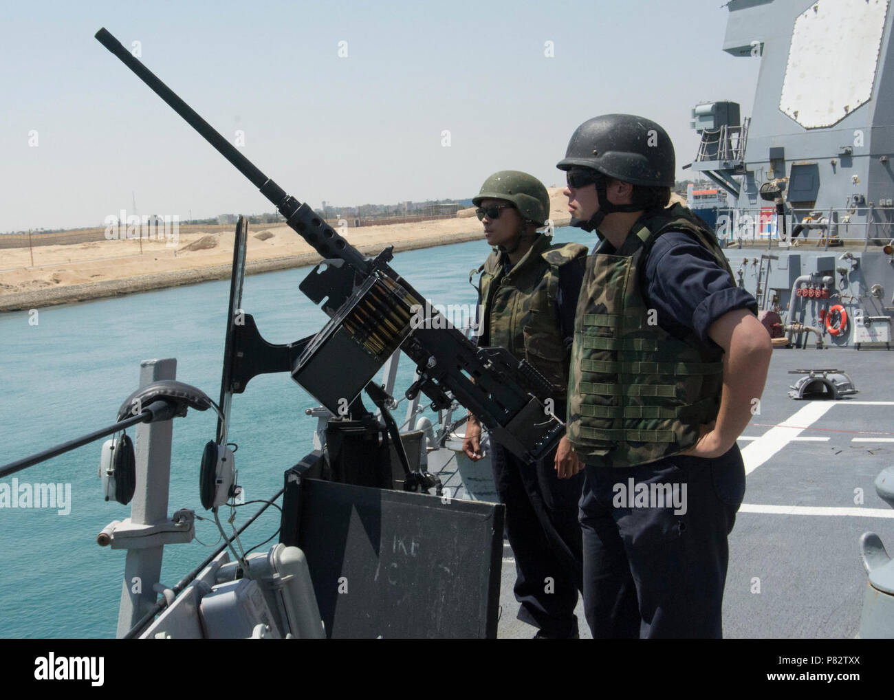 CANAL (June 29, 2016) Fire Controlman 2nd Class Ariana Friedrichs, right, and Information Systems Technician 3rd Class Phillip Aradanas man a .50-caliber machine gun while transiting the Suez Canal aboard the guided-missile destroyer USS Mason (DDG 87). Mason, deployed as part of the Eisenhower Carrier Strike Group, is supporting maritime security operations and theater security operations in the U.S. 5th Fleet area of operations. Stock Photo