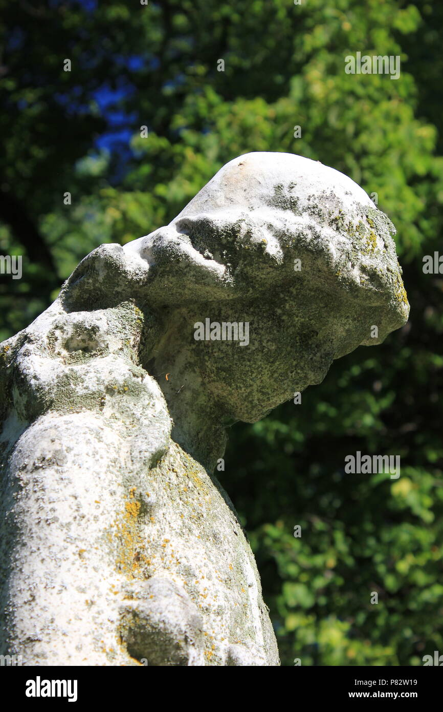 Grieving Angel stone statue at the Bohemian National Cemetery in Chicago, Illinois on a beautiful summer day. - Stock Image
